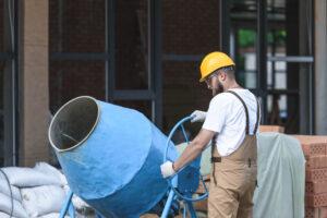homem na obra usando uma betoneira