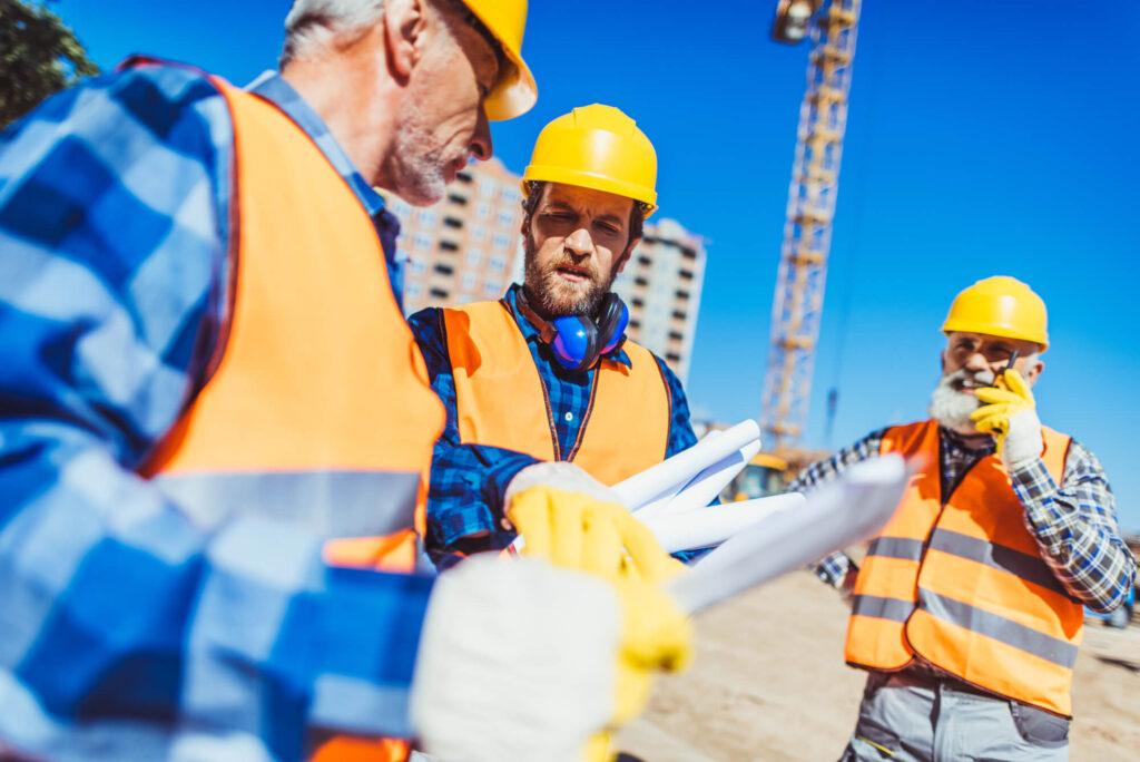 3 engenheiros em uma obra discutindo sobre o projeto