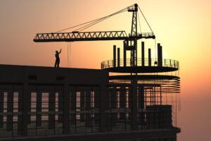 homem com um guindaste em cima de um prédio em construção