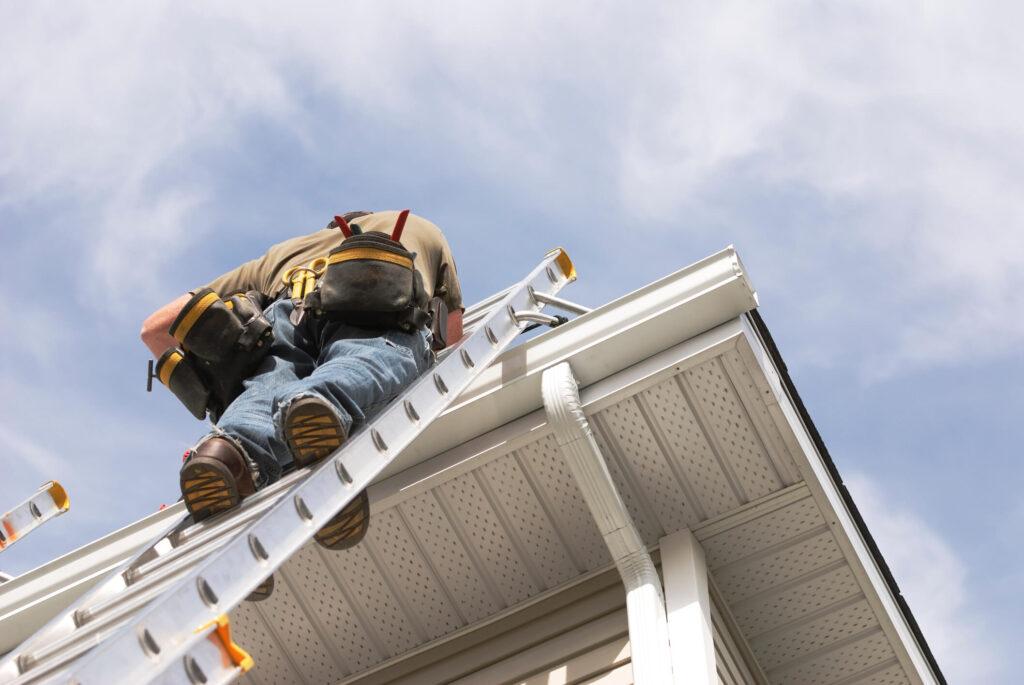 homem subindo no telhado usando uma escada