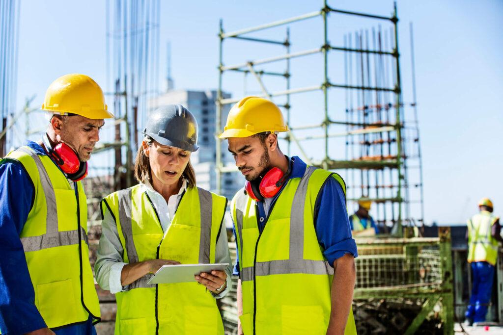 três engenheiros discutindo sobre fornecedor para construção civil