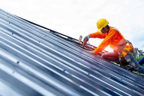 homem parafusando telha metálica