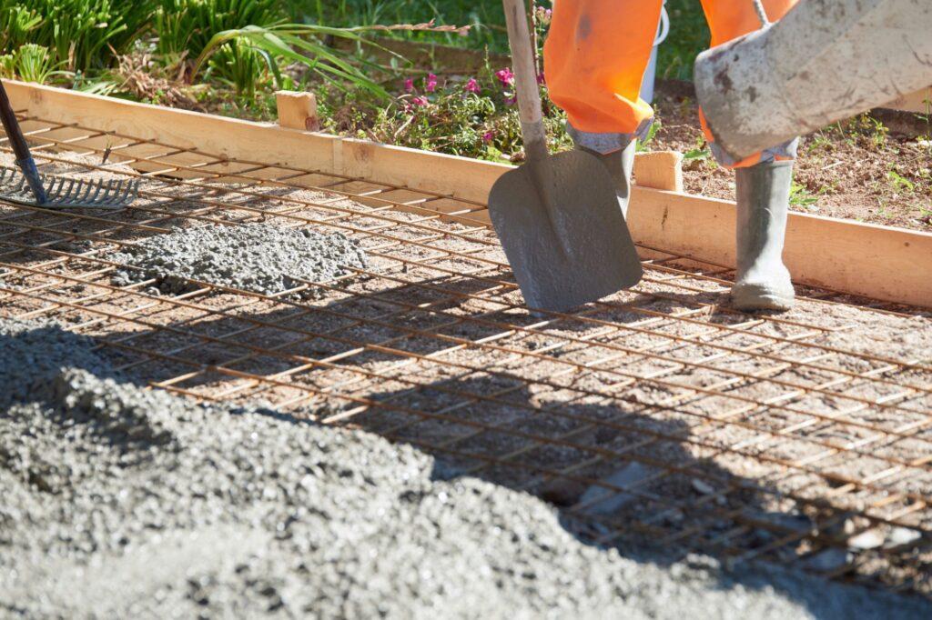 homem aplicando concreto protendido na obra