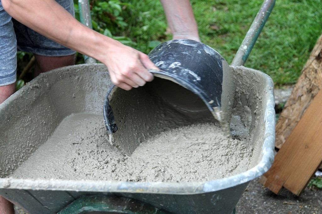 homem pegando cimento verde com o balde